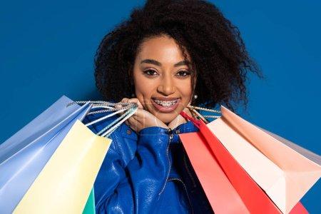 Photo pour Une Américaine d'origine africaine souriante avec des orthèses et des sacs de magasinage isolés sur bleu - image libre de droit