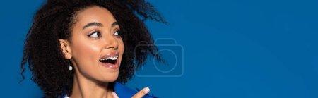 Photo pour Heureuse femme afro-américaine avec la bouche ouverte pointant du doigt isolé sur bleu, plan panoramique - image libre de droit