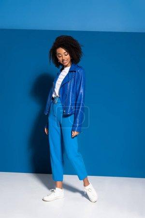 Photo pour Vue pleine longueur de souriante femme afro-américaine sur fond bleu - image libre de droit