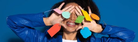 Photo for Smiling african american woman covering eyes with empty labels on hands on blue background, panoramic shot - Royalty Free Image