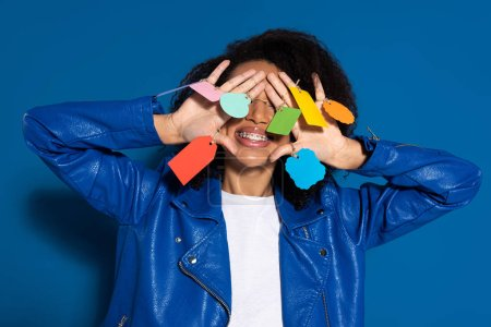 Photo for Smiling african american woman covering eyes with empty labels on hands on blue background - Royalty Free Image