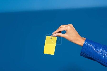 Photo pour Vue recadrée d'une femme afro-américaine tenant une étiquette vide jaune sur fond bleu - image libre de droit