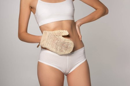 Photo pour Cropped view of slim girl with perfect skin holding scrub glove, isolated on grey - image libre de droit