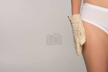 Photo for Partial view of slim girl with perfect skin holding exfoliation glove, isolated on grey - Royalty Free Image