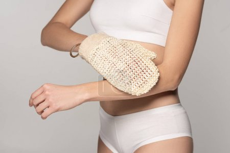 Photo pour Cropped view of woman with perfect skin using exfoliation glove, isolated on grey - image libre de droit