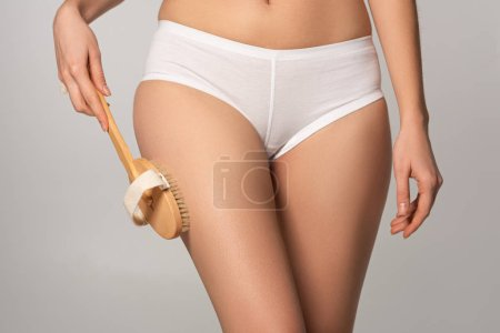 Photo for Cropped view of woman using dry massage brush, isolated on grey - Royalty Free Image