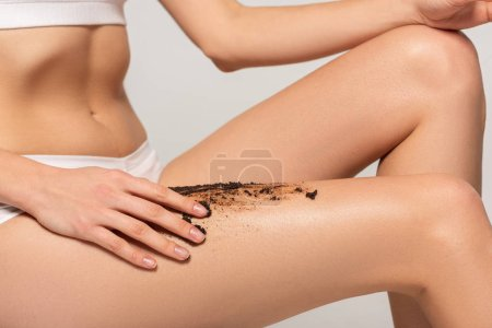 Photo for Cropped view of girl applying coffee scrub on legs, isolated on grey - Royalty Free Image