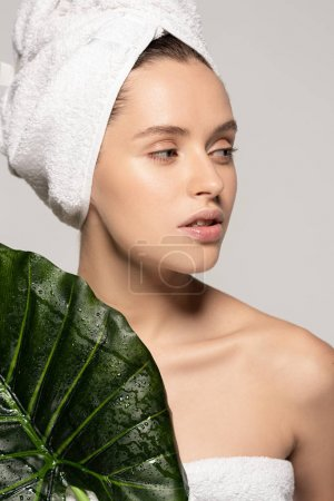 beautiful young woman with towel on head holding green leaf, isolated on grey