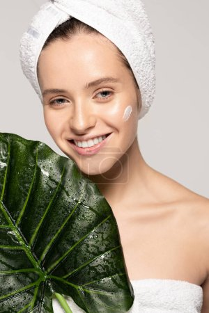 Photo for Happy girl with moisturizing cream on face and towel on head posing with green leaf, isolated on grey - Royalty Free Image
