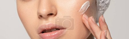 Photo for Panoramic shot of young woman applying cosmetic cream on face, isolated on grey - Royalty Free Image