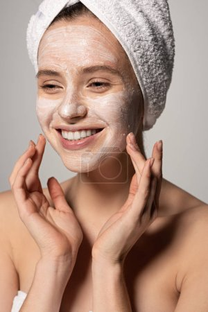 Photo pour Attractive happy girl with cosmetic mask on face and towel on head, isolated on grey - image libre de droit