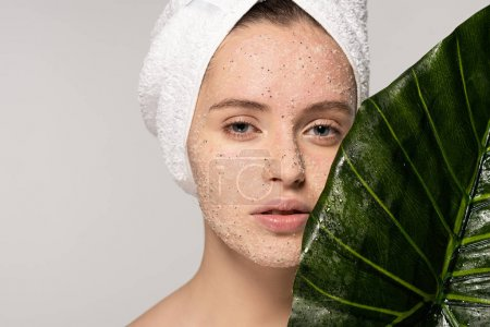 beautiful girl with towel on head and coconut scrub on face posing with leaf, isolated on grey