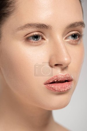 Photo pour Beautiful girl with coconut scrub on lips, isolated on grey - image libre de droit