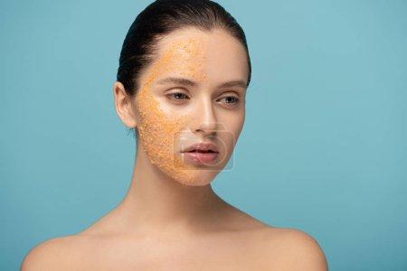 Photo pour Jolie fille appliquant du sucre jaune exfoliant sur le visage, isolé sur bleu - image libre de droit