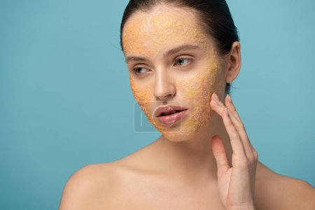 Photo for Beautiful young woman applying yellow sugar scrub on face, isolated on blue - Royalty Free Image
