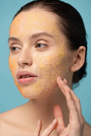 Photo pour Attractive girl applying yellow sugar scrub on face, isolated on blue - image libre de droit