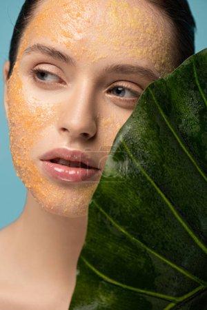 Photo pour Belle fille avec gommage de sucre sur le visage tenant la feuille, isolé sur bleu - image libre de droit