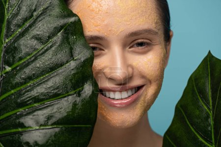 happy woman with sugar scrub on face holding leaves, isolated on blue