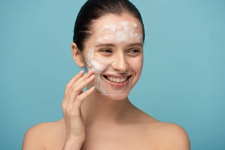 beautiful happy young woman applying cleansing foam on face, isolated on blue