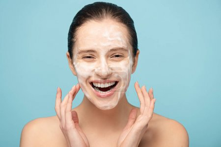 Photo for Attractive excited girl applying cleansing foam on face, isolated on blue - Royalty Free Image