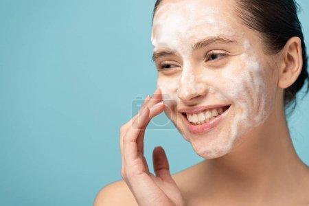 Photo pour Belle femme souriante appliquant de la mousse nettoyante sur le visage, isolée sur le bleu - image libre de droit