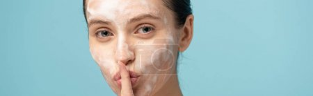 Photo pour Plan panoramique de belle jeune femme avec mousse nettoyante sur le visage montrant le symbole du silence, isolé sur le bleu - image libre de droit