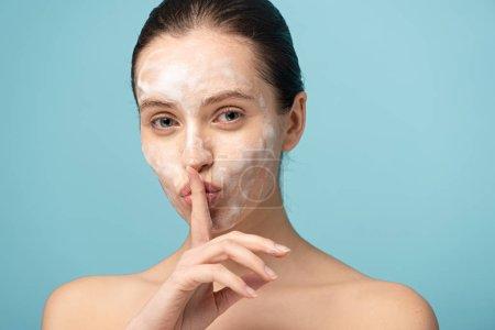 Photo pour Belle fille avec mousse nettoyante sur le visage montrant symbole de silence, isolé sur bleu - image libre de droit