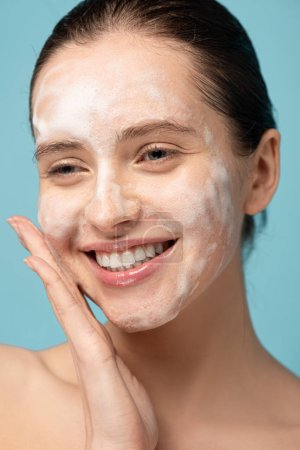 Photo pour Attrayant heureux fille appliquant mousse nettoyante sur le visage, isolé sur le bleu - image libre de droit