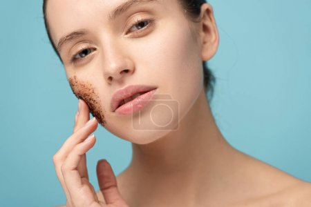Photo pour Attractive woman applying coffee scrub on face, isolated on blue - image libre de droit