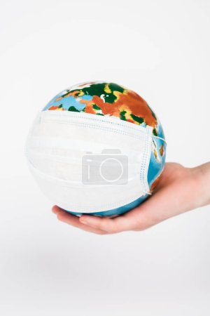 Photo pour Cropped view of woman holding globe in medical mask isolated on white - image libre de droit