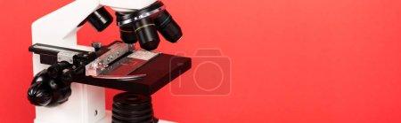 Photo pour Plan panoramique du microscope avec échantillon sur verre isolé sur rouge - image libre de droit