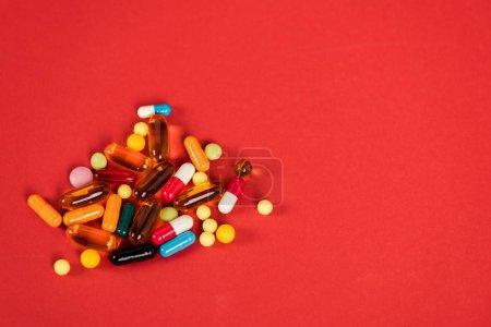 Photo pour Pilules colorées sur rouge avec espace de copie - image libre de droit