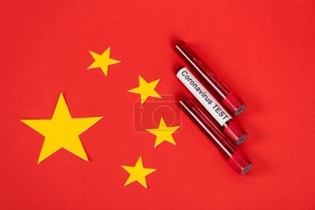 Photo pour Top view of samples with coronavirus test lettering near red chinese flag - image libre de droit