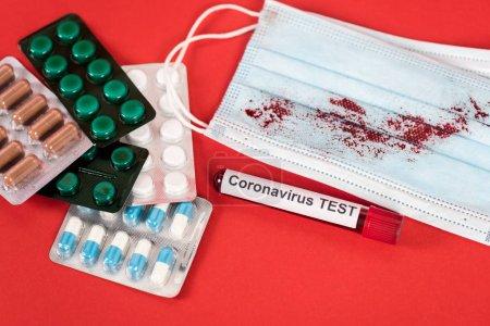 Photo pour Échantillon avec coronavirus test lettrage près des pilules et masque médical avec sang sur rouge - image libre de droit
