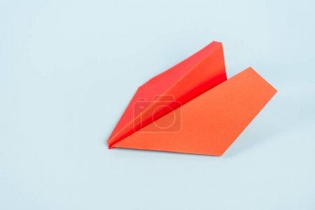 toy and orange paper plane on blue with copy space