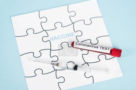 кусочки головоломки с надписью вакцины возле образца с тестом на коронавирус и шприц на голубом