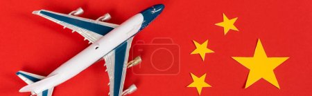 panoramic shot of toy airplane on red chinese flag