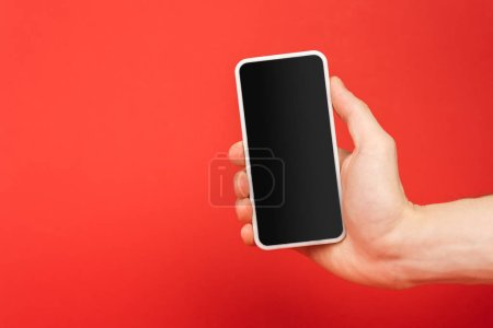 Photo for Cropped view of man holding smartphone with blank screen isolated on red - Royalty Free Image