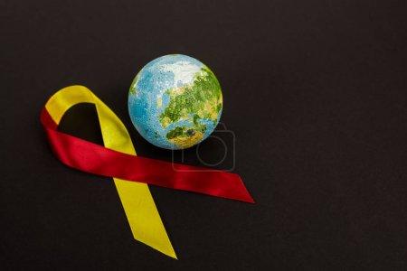 Photo pour Globe près du ruban rouge et jaune comme sensibilisation à l'hépatite c isolée sur noir - image libre de droit