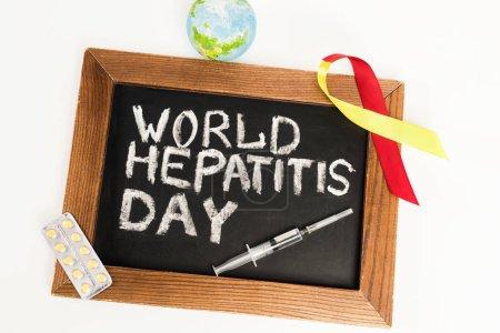Photo pour Vue du dessus du tableau avec lettrage de la journée mondiale de l'hépatite près du ruban, globe, pilules et seringue isolés sur blanc - image libre de droit