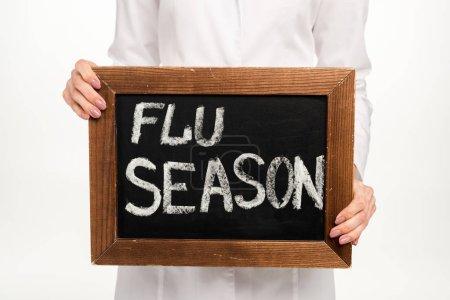 Foto de Vista recortada del médico sosteniendo pizarra con letras de la temporada de gripe aislado en blanco - Imagen libre de derechos