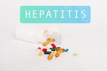 Photo pour Bouteille près de pilules colorées et lettrage hépatite sur blanc - image libre de droit