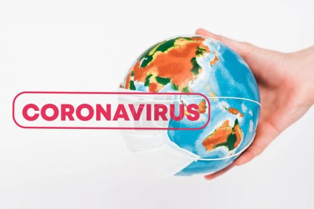 Photo pour Cropping view of man holding globe in protective mask near coronavirus lettering on white - image libre de droit