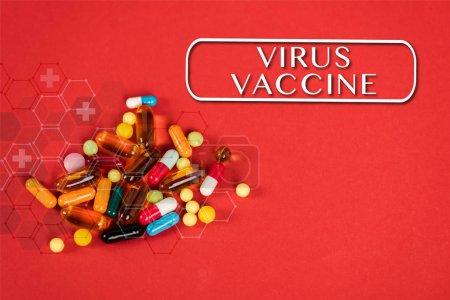 Photo pour Pilules colorées près du monde lettrage hépatite jour sur rouge - image libre de droit