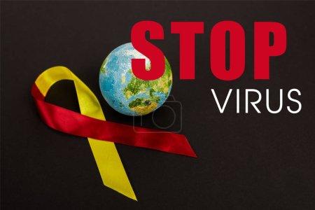 Photo pour Ruban rouge et jaune près du globe et arrêter le lettrage du virus sur noir - image libre de droit