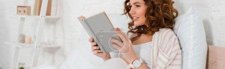 Photo pour Vue panoramique de la femme enceinte souriant tout en lisant le livre sur le lit - image libre de droit