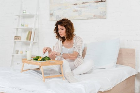 Photo for Beautiful pregnant woman eating salad near glass of milk on breakfast tray - Royalty Free Image