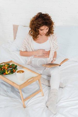 Schwangere liest Buch bei Tasse Tee und Salat auf Frühstückstablett im Bett