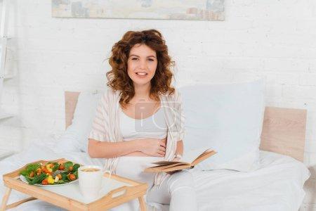 Schwangere mit Buch lächelt in die Kamera bei Tasse Tee und Salat auf dem Frühstückstablett auf dem Bett