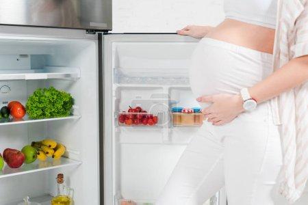 Photo pour Vue recadrée de la femme enceinte ouvrant réfrigérateur avec des légumes et des fruits frais sur fond blanc - image libre de droit
